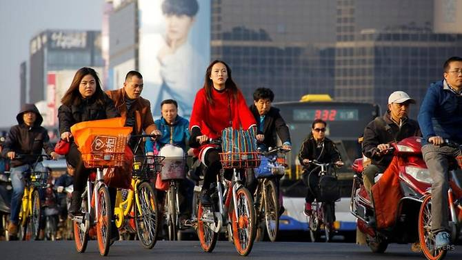 FILE PHOTO: People cross a busy street on bicycles and electric scooters in central Beijing, China, October 12, 2017. (Photo: REUTERS/Thomas Peter/File photo)