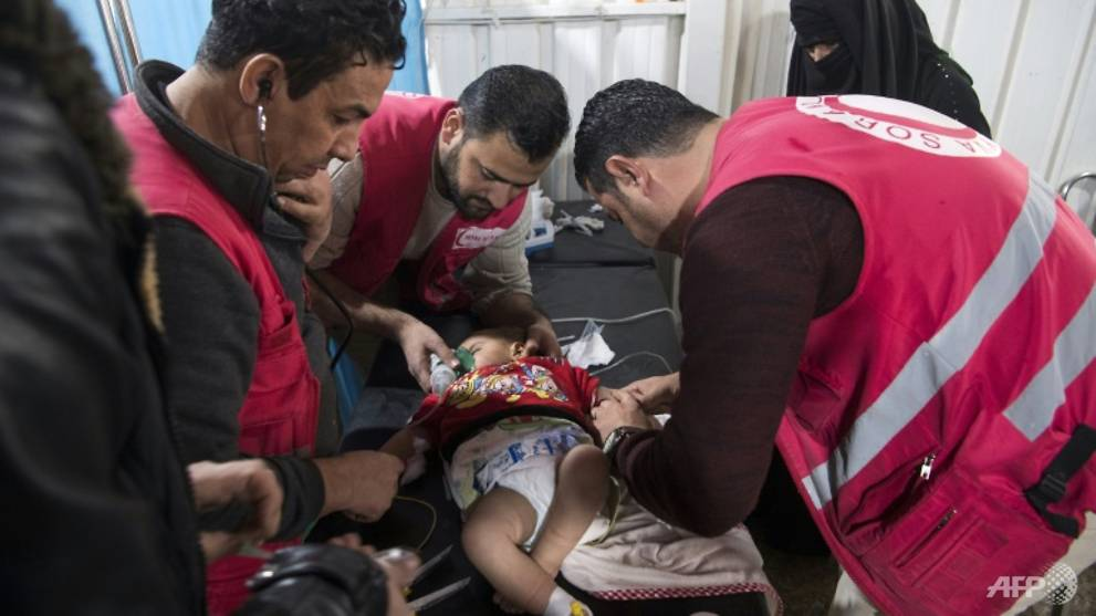 Syrian medics treat a baby at a camp clinic in Al-Hol but dozens have had to be rushed to hospital