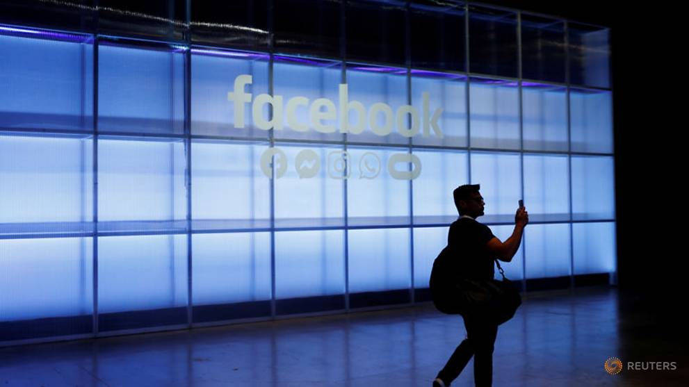 File photo  an attendee takes a photograph of a sign during facebook inc s f8 developers conference in san jose 1