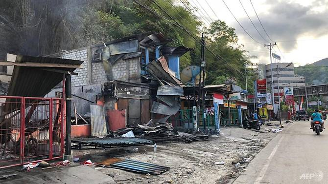 residents-ride-motorcycles-next-to-torched-shops-in-jayapura.jpg
