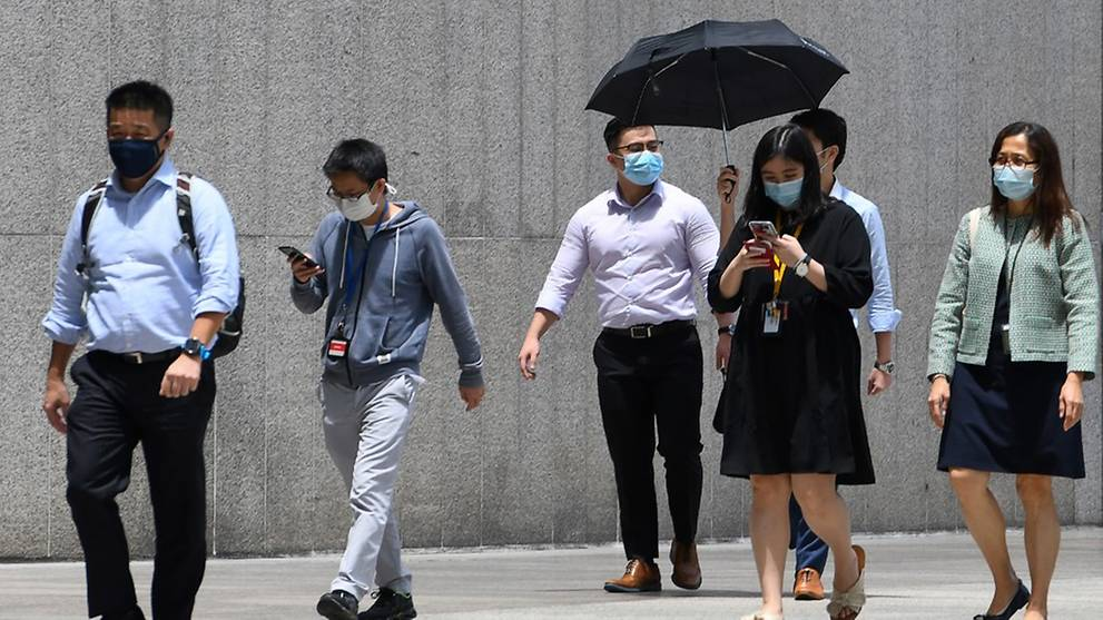 People walk out of their office building as they head for their lunch break in Singapore on Sep 30, 2020. (File photo: AFP/Roslan Rahman)