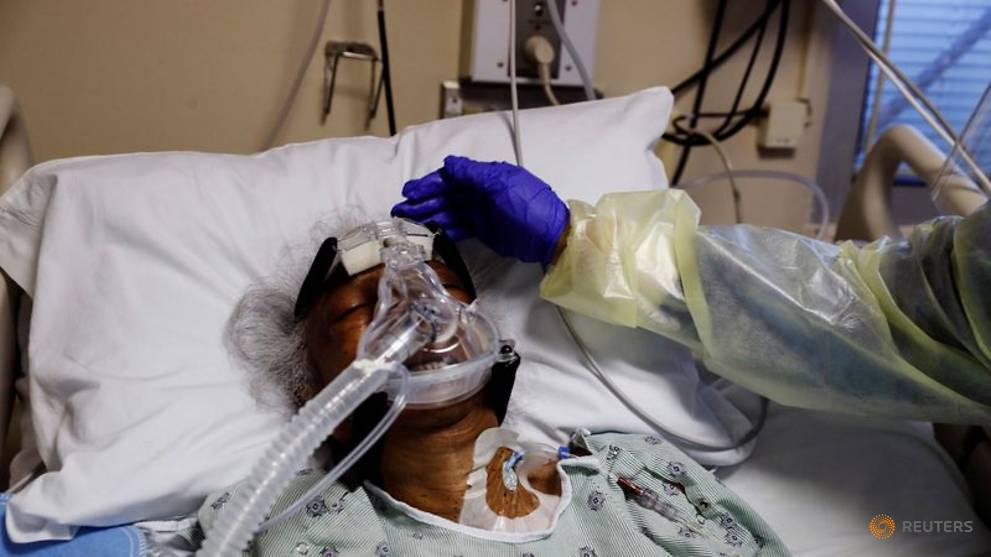 FILE PHOTO: Florence Bolton, 86, a coronavirus disease (COVID-19) positive patient, has her head touched by registered nurse Alma Abad as she lies in her intensive care bed at Roseland Community Hospital on the South Side of Chicago, Illinois, U.S., December 1, 2020. REUTERS/Shannon Stapleton