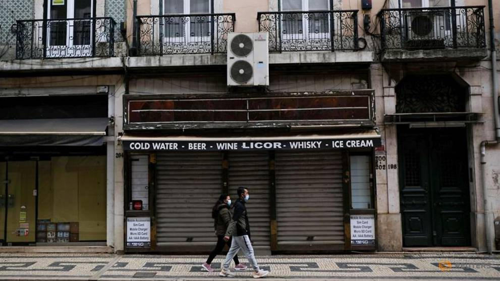 people-pass-by-closed-stores-in-lisbon-d