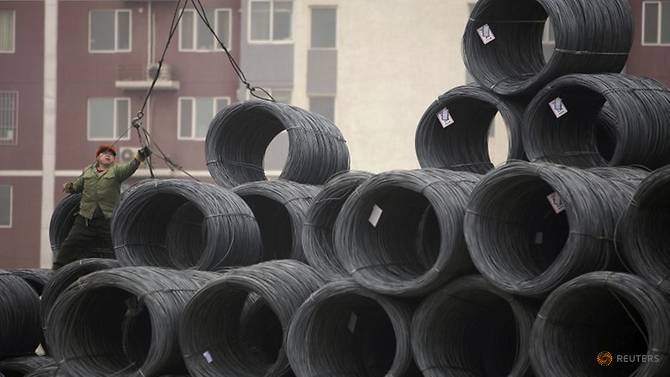 [Image: a-labourer-works-on-coils-of-steel-wire-...jing-1.jpg]